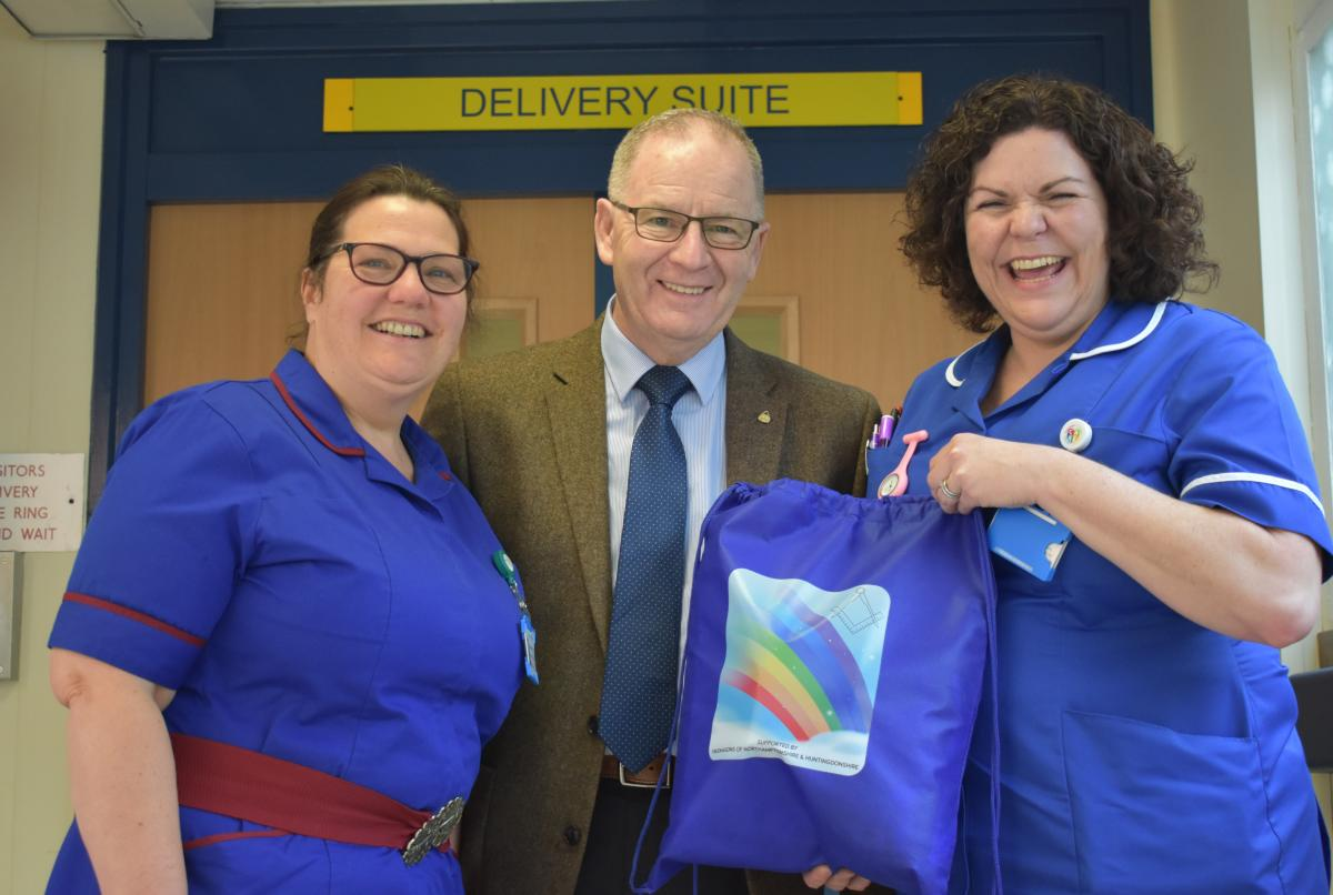 Stephanie Fretter and Carolyn Rowbotham receive rainbow bags from Gerry McLaughlin of Freemasons
