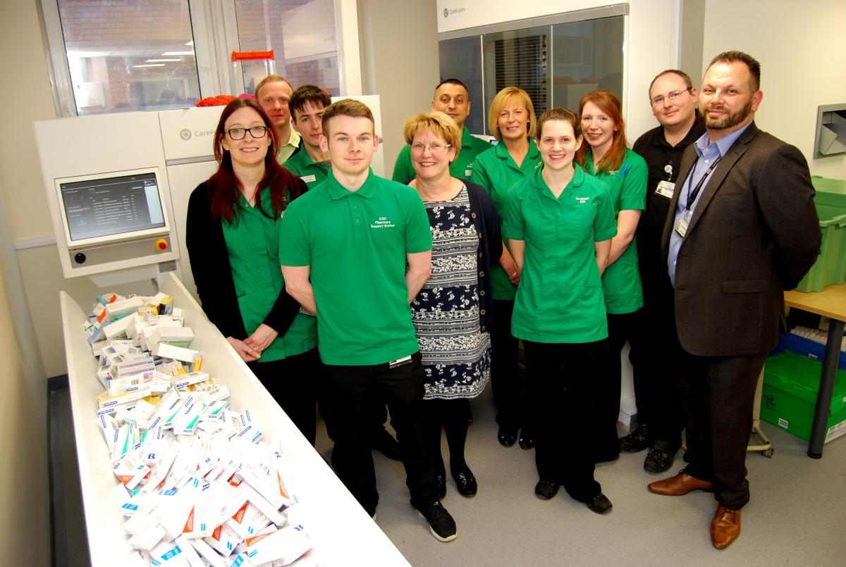 Photo of Pharmacy Team standing near robot dispenser